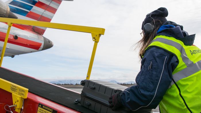 female agent unloading baggage from ramp