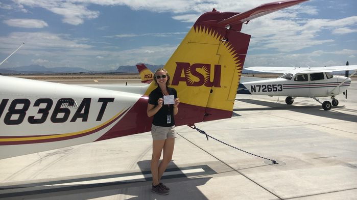 Megan in front of an ASU plane holding her commercial multi-engine license