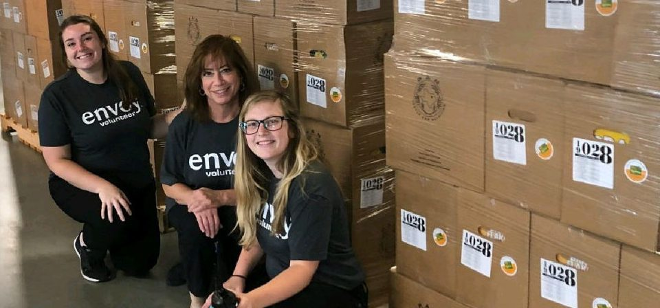 three female envoy employees pose for a photo while volunteering at the north texas food bank
