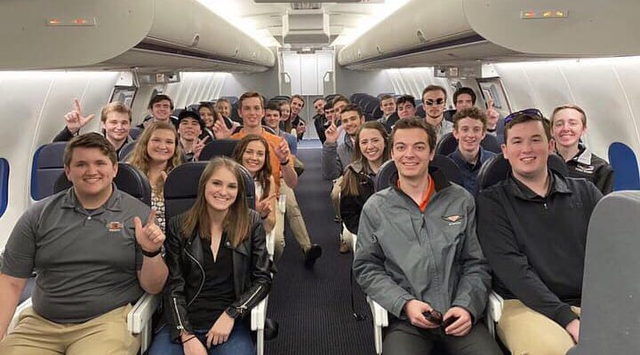 Flying Aggies students pose on a cabin trainer