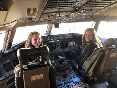 Two female OSU students pose in the flight deck of a 777