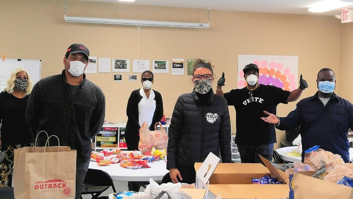 Meal & Gift Bag Distribution Me with blue mask and arms wide open in my Envoy uniform. The others are volunteers