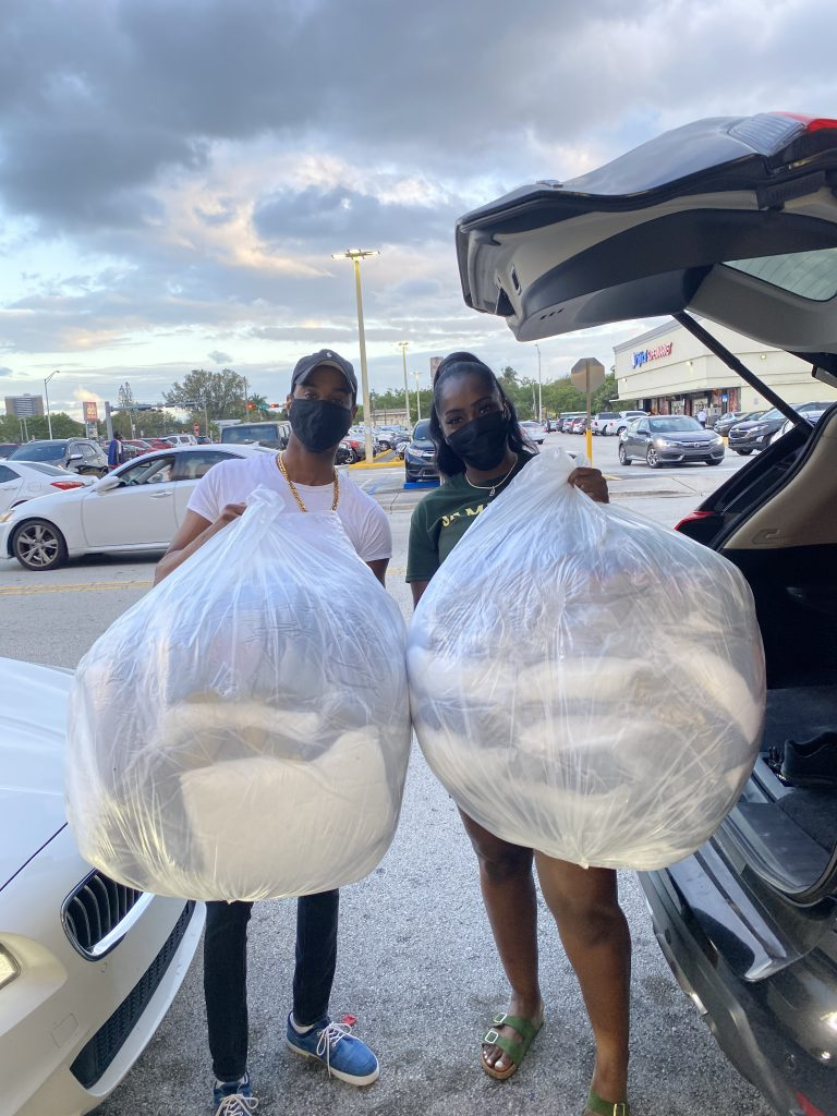 Captain Anselm Dewar (left) with Brandy Jackson, CEO of Bee-Kind (right), with bags of donated blankets and pillows. (Photo courtesy of Anselm Dewar)
